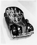 [Packard Automobile with Six Passengers Seen through Graphic Cut-away of the Roof]