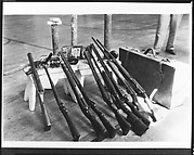 [Copy of Newspaper File Photograph: Nine Guns Propped on Bench Next to Valise, Probably Havana]