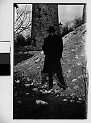 [Hanns Skolle in Overcoat and Hat Before Stone Tower]