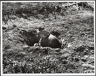 His own garden provides this man with an air raid shelter, Hankow