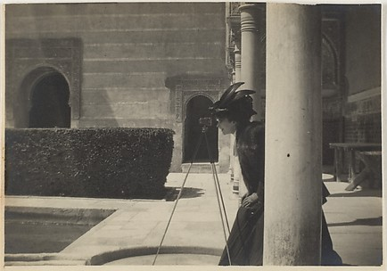 [View of a Courtyard with a Woman (Olga?) Looking Through a Camera on a Tripod]