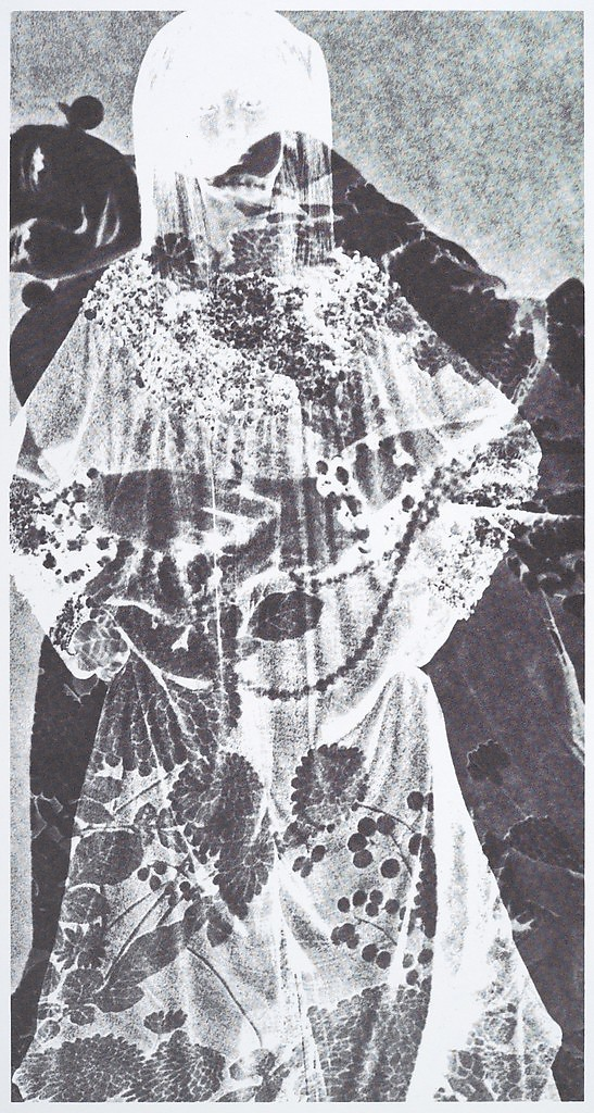[Pale figure in flowered robe]