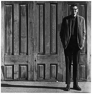 [Man Standing in Front of Three Wooden Doors]