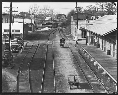 [Railroad Tracks Through Town with Parked Cars, Depot, and Pedestrians, Edwards, Mississippi]