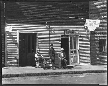 [Men on Sidewalk in Front of New Deal and Savoy Barber Shops, Vicksburg, Mississippi]