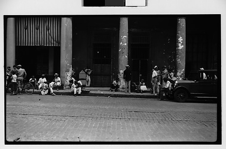 [Street Scene with Men Standing and Seated on Sidewalk, Havana]