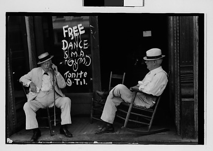 [Two Elderly Men in Conversation on Porch in Front of Painted Sign for