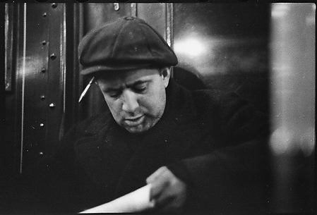 [Subway Passenger, New York City: Man in Cap Reading Newspaper]