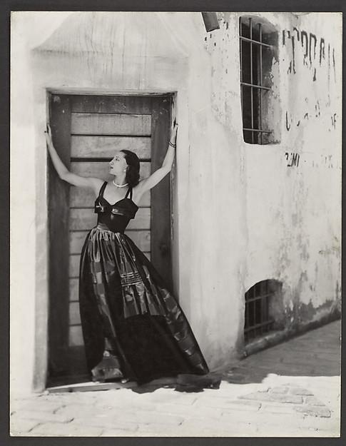 [Woman in Long Dress, Standing in Doorway of Stuccoed Building]