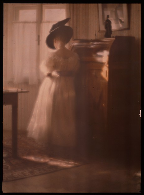 [Lady in White Dress Leaning Against Desk]