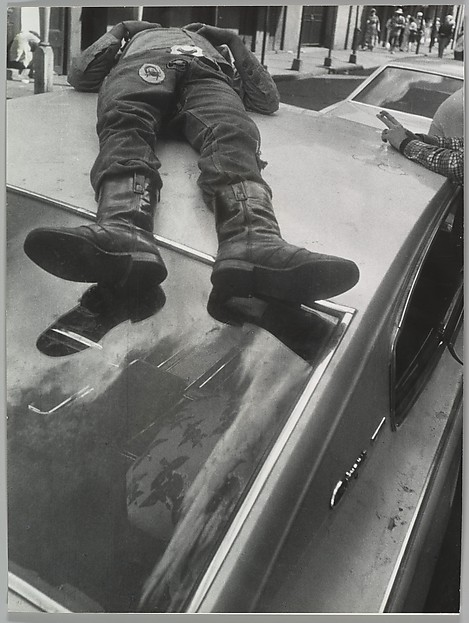 [Man Lying on Roof of Car]