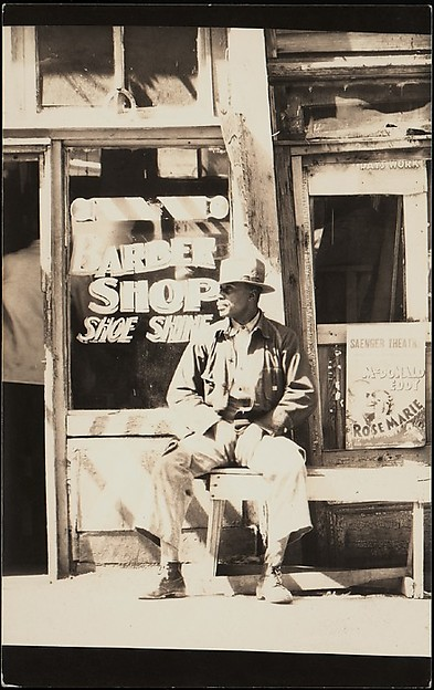 [Man Seated Outside Barber Shop, Vicksburg, Mississippi]
