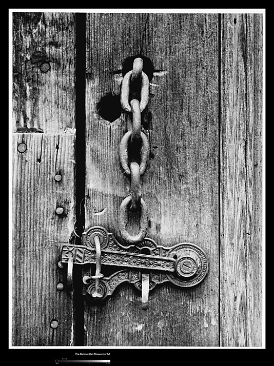 a black and white photograph of an worn wooden door with a heavy old chain coming out of it. Below the chain is an intricate metal latch.