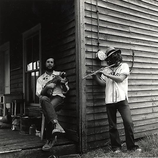 [Two Men, One Seated on Porch Holding Raccoon, One Standing by House Playing Flute]