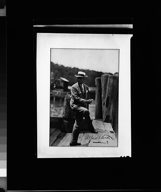 [Copy of Signed Photograph of Alfred E. Smith, Governor of New York, Standing on Dock in Suit and Hat, Eating Sandwich]