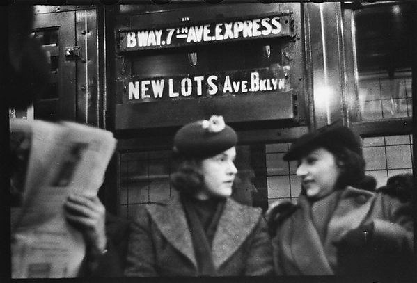 """[Subway Passengers, New York City: Two Women in Conversation Beneath """"Broadway 7th Ave Express"""" Sign]"""
