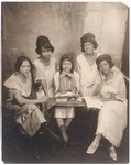 [Five Young Women Posed Around Table]