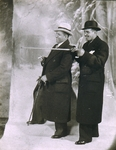 [Two Men in Overcoats, One Gesturing with Cane, Posed in Front of Painted Backdrop]