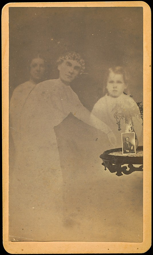 [Three Spirits with Photograph on Table]