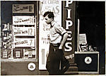 [Young Man Passing Drugstore and Cigar Store, New York City]