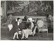 [Two Women, Seated and in Conversation, in Interior Setting]