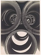 [Water Pipe Abstraction; View through Circular Ends of 3 Stacked Pipes onto Rows of Stacked Pipes in Background]
