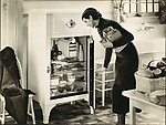[Advertisement for Westinghouse Refrigerators: Woman Putting Groceries Away]