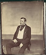 [Seated Man in White Vest and Dark Coat]