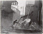 After incendiary bombardments, a woman tries futilely to extinguish the fire. Hankow