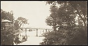 [View of a Bridge leading to a House over a Body of Water]