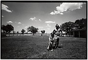 [Woman Seated in Chair on Lawn with Man Standing Alongside]
