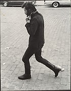 [Street Scene: Man in Boots Walking and Adjusting His Collar, New York City]