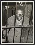 [Man Looking through Prison Bars]