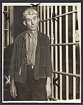 [Man Leaning against Prison Bars]