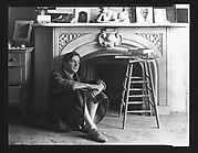[Reuben Nakian Seated Against Fireplace Mantle]