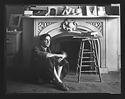 [Reuben Nakian Seated in Front of Fireplace Mantle]