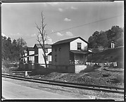 "[Row of Clapboard ""Company"" Houses for Miners Along Railroad Tracks and Creek, Osage, West Virginia]"