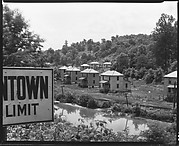 """[""""Company"""" Houses for Miners by Train Tracks and Creek (with Town Sign in Foreground), Masontown, West Virginia]"""