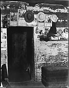 [Advertisements and Straw Hats on Wall Around Entrance to Frank Tengle's Bedroom, Hale County, Alabama]