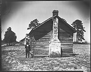 [Man Posing for Picture in Front of Wooden House]