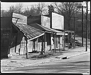 [Oblique View of Roadside Stores with Ads for 666 Cold Remedy, Vicksburg, Mississippi]