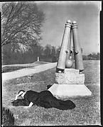 [Peter Sekaer Wrapped in Dark Cloth Lying on Ground Next to Battlefield Monument, Vicksburg, Mississippi]