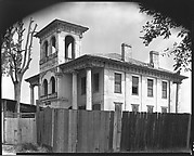 [Converted Italianate Revival House with Wrecking Company Signs on Tower Behind Wooden Fence, Near Tuscaloosa, Alabama]
