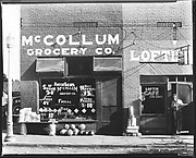 [Main Street Façades of McCollum Grocery Company and Loftis Cafe with Man in Doorway, Greensboro, Alabama]