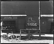 [Painted Shopfront Façade of City Shine Parlor with Bicycle in Front]