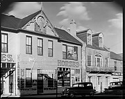 [Storefront Façades Including Lum Brothers Stables with Parked Cars on Street, Natchez, Mississippi]