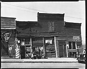 [Row of Shopfronts with Men Seated on Bench on Sidewalk, Vicksburg, Mississippi]