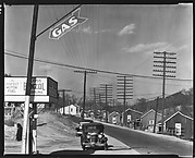 [Roadside Gas Station with Parked Cars and Row of Miners' Houses Across Street, Lewisburg, Alabama]
