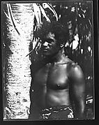 [South Seas: Man Wearing Sarong Next to Palm Tree]