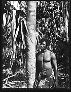 [South Seas: Man in Sarong Standing Next to Tree]